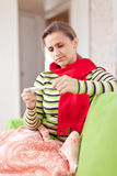 Sick woman looks by thermometer Stock Image