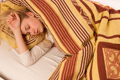 Sick woman lying in bed covered with blanket, feeling ill, has f Royalty Free Stock Photography