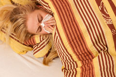 Sick woman lying in bed covered with blanket, feeling ill, has f Stock Image