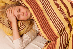 Sick woman lying in bed covered with blanket, feeling ill, has f Stock Photography