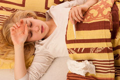 Sick woman lying in bed covered with blanket, feeling ill, has f Royalty Free Stock Image