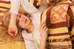 Sick woman lying in bed covered with blanket, feeling ill, has f Stock Photo
