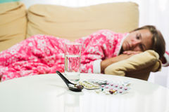 Sick woman lying in bed in dressing gown looking at thermometer and pills Royalty Free Stock Images