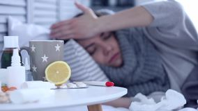 Sick woman lying on bed with flu at grey bedroom stock footage