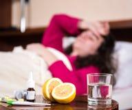Sick woman lying at bed Royalty Free Stock Image