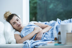Sick woman lying in bed Royalty Free Stock Photos