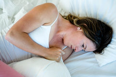 sick woman lying in bed looking unwell Royalty Free Stock Photos