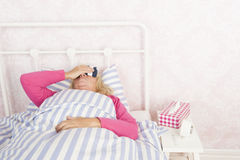 Sick woman lying in bed Stock Images