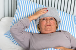 Sick Woman Lying on Bed with Towel on the Forehead Stock Image