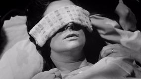 Sick woman lying down with a washcloth over her eyes stock video footage