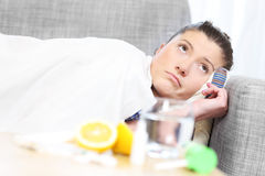 Sick woman lying on a sofa Royalty Free Stock Photo