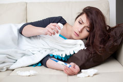 Sick woman lying with thermometer Stock Image
