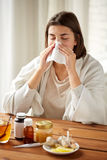 Sick woman with medicine blowing nose to wipe Stock Photo