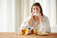 Sick woman with medicine blowing nose to wipe Stock Image
