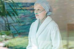 Sick woman in nasal cannula. Sick woman in headscarf and nasal cannula looking through window Stock Photo