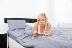 Sick woman with pack of pills lying on bed Royalty Free Stock Image