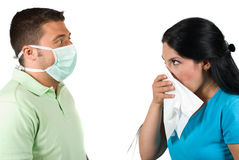 Sick woman and paranoia man. Sick woman having flu and sneeze in a white napkin and the man are terrified,wearing a protective mask  and making big eyes  when Royalty Free Stock Images