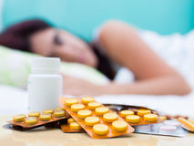 Sick woman and pills from her medical treatment. Out of focus woman resting in bed with some pills from her medical treatment on a table in the foreground royalty free stock images