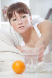 Sick woman reaching for glass water Royalty Free Stock Photos