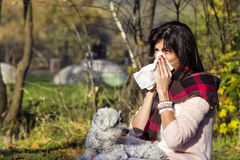 Sick woman relaxing in the autumn park with her dog. Sick Woman.Flu.Woman Caught Cold. Virus .Medicines stock photography