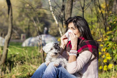 Sick woman relaxing in the autumn park with her dog. Sick Woman.Flu.Woman Caught Cold. Virus .Medicines royalty free stock image