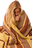 Sick woman sitting on bad wrapped in a blanket feeling ill, has Royalty Free Stock Image