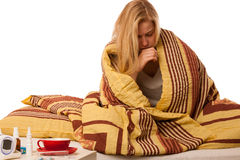 Sick woman sitting on bad wrapped in a blanket feeling ill, has Stock Image