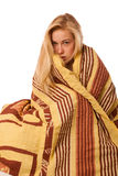 Sick woman sitting on bad wrapped in a blanket feeling ill, has Royalty Free Stock Images