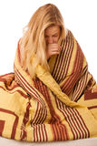 Sick woman sitting on bad wrapped in a blanket feeling ill, has Stock Images
