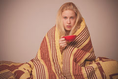 Sick woman sitting on bad wrapped in a blanket feeling ill, has Stock Photography