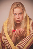 Sick woman sitting on bad wrapped in a blanket feeling ill, has Royalty Free Stock Photos