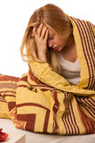 Sick woman sitting on bad wrapped in a blanket feeling ill, has Royalty Free Stock Photo