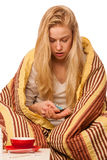 Sick woman sitting on bad wrapped in a blanket feeling ill, has Stock Photo