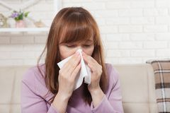 Sick woman sitting at home with high fever. Cold, flu, fever and migraine, sneeze. Copy space. Runny nose.  Stock Images