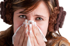 Sick Woman Sneezing. Pale sick woman with a flu, sneezing, in a white background Royalty Free Stock Photography