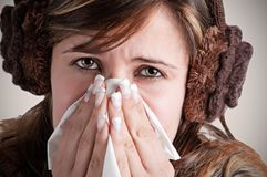 Sick Woman Sneezing. Pale sick woman with a flu, sneezing, in a dark background Royalty Free Stock Images
