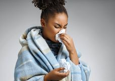 Sick woman sneezing and blowing nose. Photo of african american woman wrapped in paid on gray background. Medical concept stock images