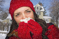 Sick Woman In Snow Blowing Her Sore Nose With Tissue. Miserable Sick Woman In Falling Snow Blowing Her Sore Nose With Tissue Outside stock photos