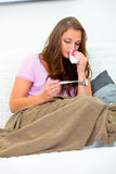 Sick woman on sofa looking at thermometer Royalty Free Stock Photos