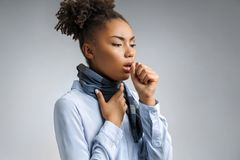 Sick woman with sore throat. Photo of african american woman in blue shirt suffering virus of flu on gray background. Medical concept stock photos