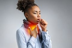 Sick woman with sore throat. Photo of african american woman in blue shirt suffering virus of flu on gray background. Medical concept stock image