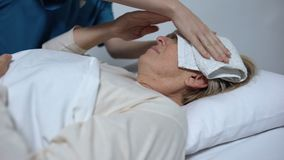 Sick woman suffering from fever and ravings, nurse putting compress on forehead. Stock footage stock footage