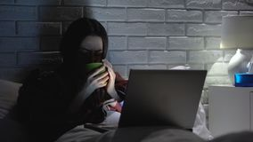 Sick woman suffering flu fever, drinking tea watching movie, home treatment. Stock footage stock video footage