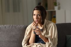 Sick woman taking painkiller pill looking at camera. Sitting on a couch in the living room at home Royalty Free Stock Photos