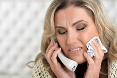 Sick woman talking on the phone Royalty Free Stock Photos