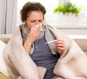 Sick Woman with Thermometer. Flu. Sneezing into Tissue Stock Photos