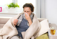 Sick Woman with Thermometer. Flu. Sneezing into Tissue Stock Photo