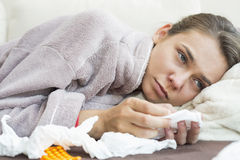Sick woman with tissue and medicines lying on bed Stock Photos