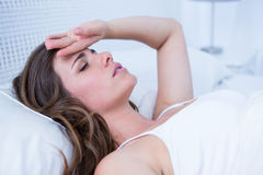 Sick woman touching her forehead Stock Photography