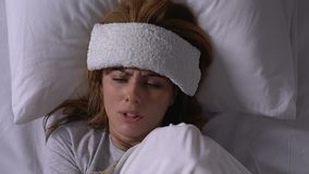 Sick woman with towel on forehead shivering with cold in bed, flu symptoms. Stock footage stock footage